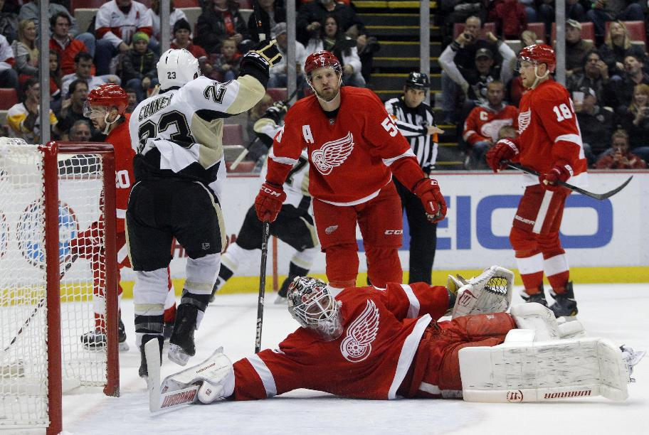 Pittsburgh Penguins' Chris Conner (23) celebrates a goal by teammate Sidney Crosby as Detroit Red Wings goalie Jonas Gustavsson (50), of Sweden, lies on the ice and Niklas Kronwall (55), of Sweden, skates away during the third period of an NHL hockey game on Saturday, Dec. 14, 2013, in Detroit. The Penguins defeated the Red Wings 4-1
