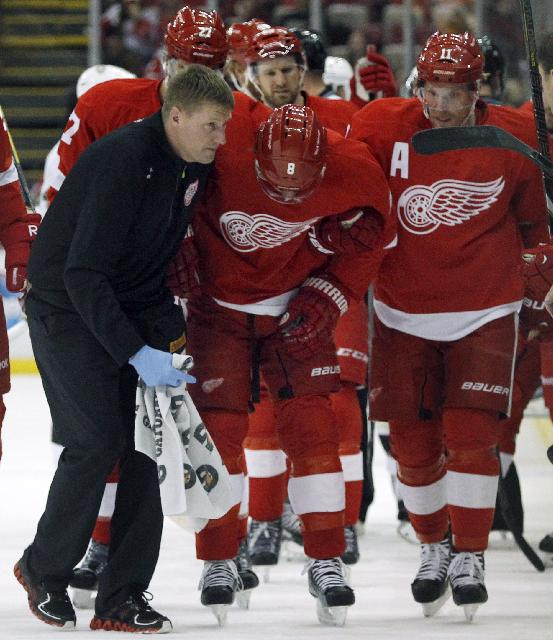 Detroit Red Wings' Justin Abdelkader (8) is helped off the ice by trainer Piet Van Zant, left, and teammate Daniel Alfredsson (11) after an illegal hit to the head by Pittsburgh Penguins' Deryk Engelland (5) during the first period of an NHL hockey game on Saturday, Dec. 14, 2013, in Detroit. Engelland was immediately assessed a match penalty and ejected from the game