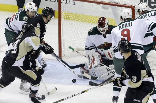 Pittsburgh Penguins' Pascal Dupuis (9) gets to a rebound off Minnesota Wild goalie Niklas Backstrom (32) and gets it past Backstrom for a goal in the first period of an NHL hockey game in Pittsburgh, Thursday, Dec. 19, 2013