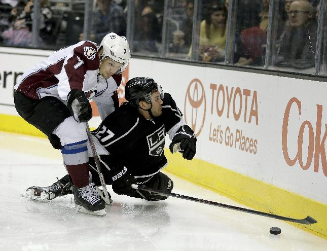 Colorado Avalanche center John Mitchell, left, knocks Los Angeles Kings defenseman Alec Martinez to the ice during the third period of an NHL hockey game, Saturday, Dec. 21, 2013, in Los Angeles