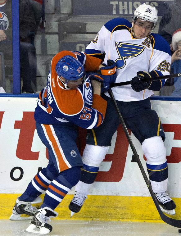 St. Louis Blues' Alexander Steen (20) is checked by Edmonton Oilers' David Perron (57) during the second period of an NHL hockey game in Edmonton, Alberta, on Saturday, Dec. 21, 2013