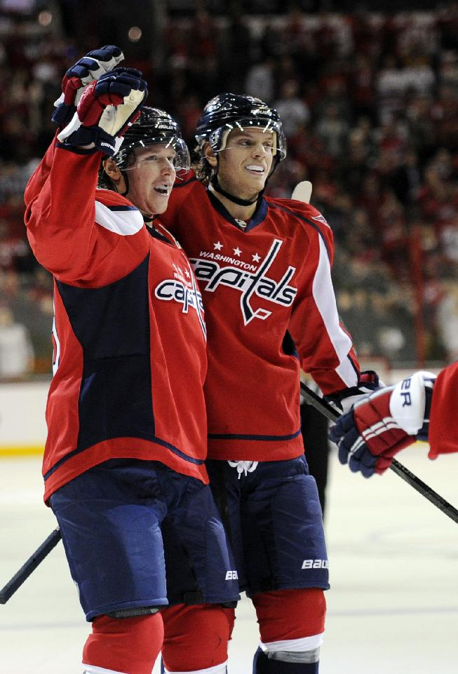 Washington Capitals center Nicklas Backstrom, left, of Sweden, celebrates his goal with John Carlson, right, during the first period an NHL hockey game against the Anaheim Ducks, Monday, Dec. 23, 2013, in Washington