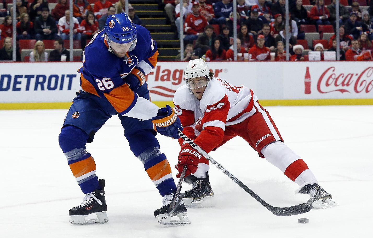 New York Islanders left wing Thomas Vanek (26), of Austria, passes around Detroit Red Wings defenseman Danny DeKeyser (65) in the first period of an NHL hockey game, Monday, Dec. 23, 2013, in Detroit