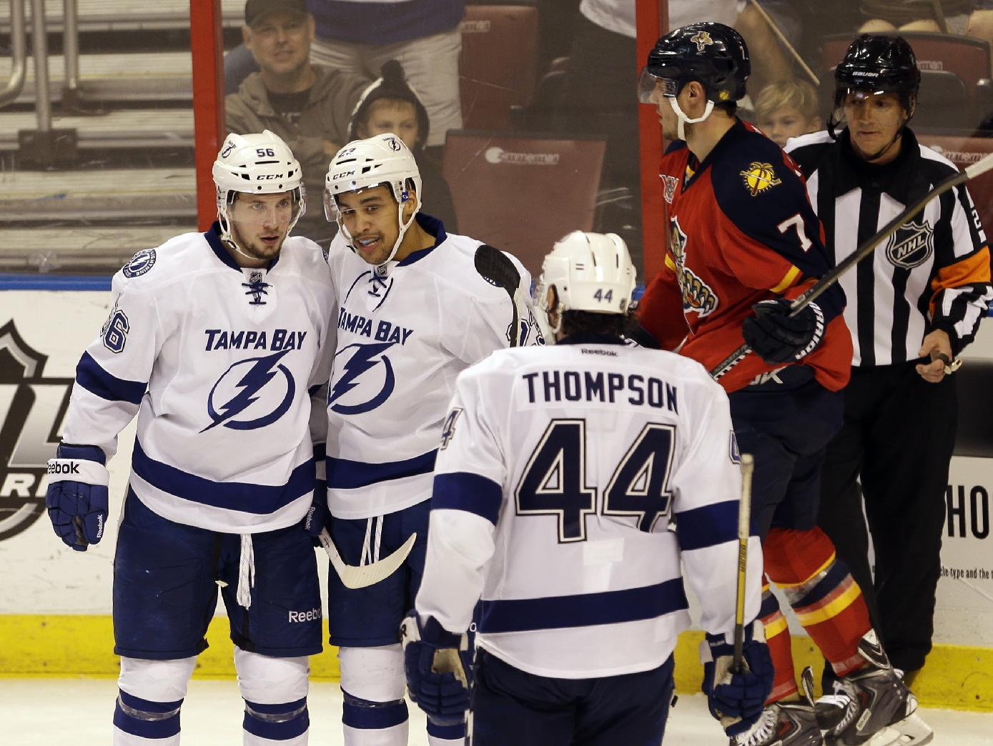 Tampa Bay Lightning right wings Nikita Kucherov (56) and J.T. Brown, second from left, celebrate after Brown scored against the Florida Panthers during the third period of an NHL hockey game in Sunrise, Fla., Monday, Dec. 23, 2013. Tampa Bay won 6-1