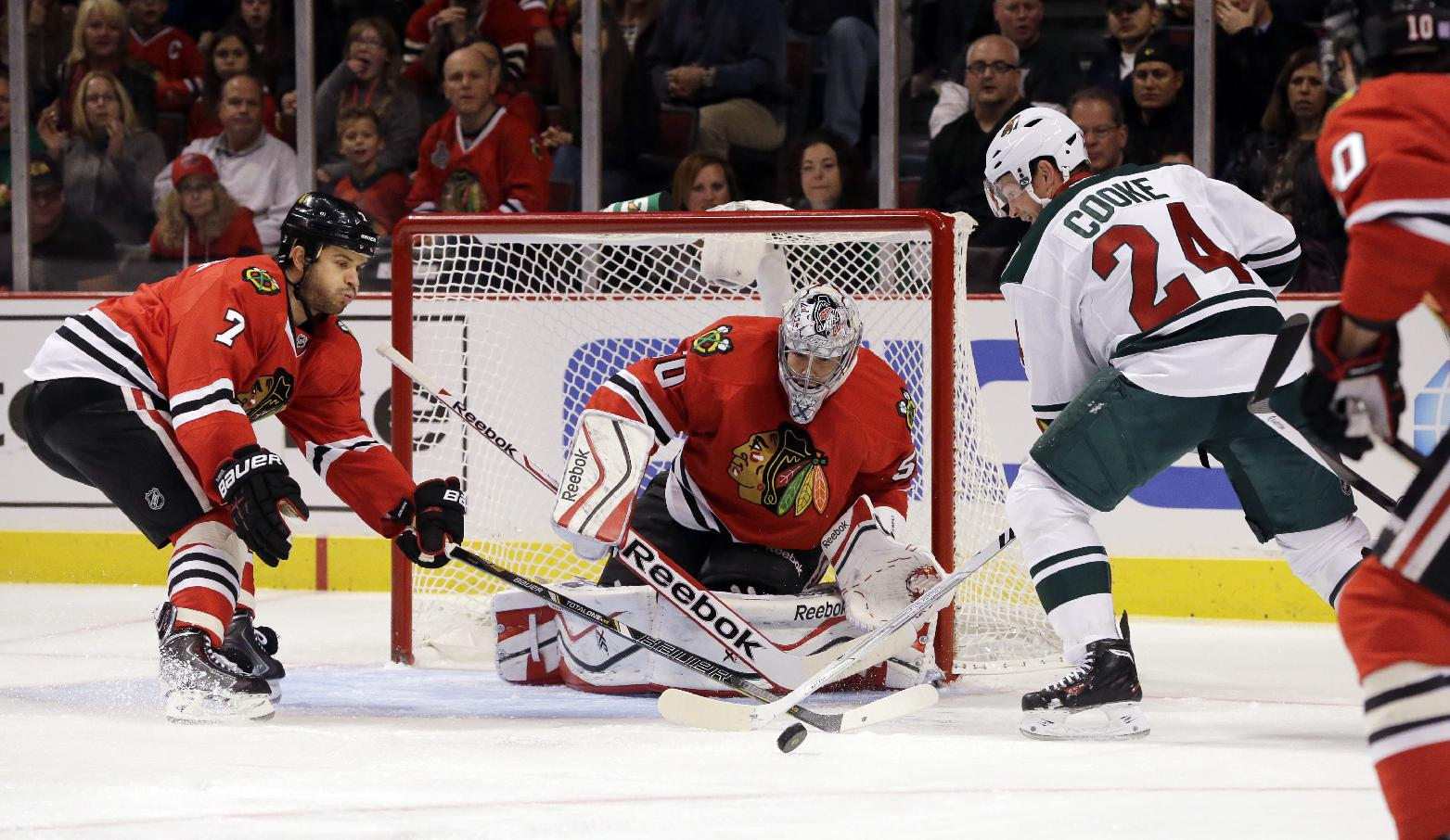 In this Oct. 26, 2013 file photo, Minnesota Wild's Matt Cooke (24) and  Chicago Blackhawks' Brent Seabrook (7) battle for the puck in front of goalie Corey Crawford (50) during the first period of an NHL hockey game in Chicago. The Chicago Blackhawks lead the NHL with 145 goals. Seabrook has three goals and 23 assists after he had 20 points in 47 games last season