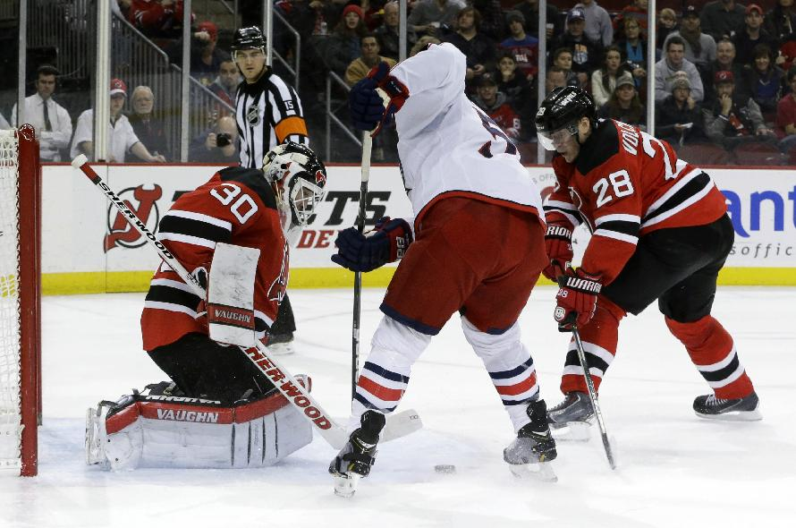 New Jersey Devils goalie Martin Brodeur, left, makes a save on a shot by Columbus Blue Jackets center Mark Letestu, center, as defenseman Anton Volchenkov (28), of Russia, defends on the play during the first period of an NHL hockey game, Friday, Dec. 27, 2013, in Newark, N.J