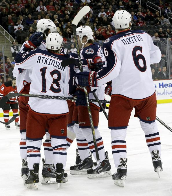 Columbus Blue Jackets center Artem Anisimov, top left, of Russia, is congratulated by teammates Cam Atkinson (13), Jack Johnson (7) and Nikita Nikitin (6), of Russia, after Anisimov scored a goal against the New Jersey Devils during the first period of an NHL hockey game, Friday, Dec. 27, 2013, in Newark, N.J