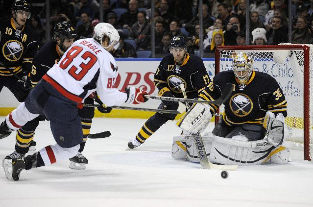 Washington Capitals' Jay Beagle (83) shoots the puck as he falls while Sabres Christian Ehrhoff (10) Mike Weber (6) Linus Omark (17) and Ryan Miller (30) defend during the second period of an NHL hockey game in Buffalo, N.Y., Sunday, Dec. 29, 2013