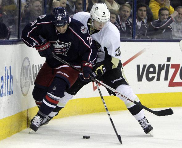 Columbus Blue Jackets' Derek MacKenzie, left, and Pittsburgh Penguins' Olli Maatta, of Finland, fight for a loose puck during the second period of an NHL hockey game, Sunday, Dec. 29, 2013, in Columbus, Ohio