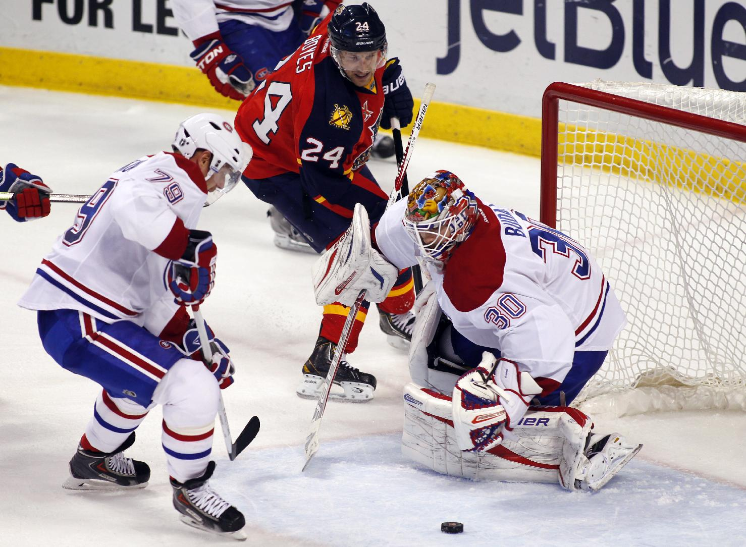 Montreal Canadiens goalie Peter Budaj (30) deflects a shot as teammate Andrei Markov (79) and Florida Panthers right wing Brad Boyes (24) go after the puck during the second period of an NHL hockey game in Sunrise, Fla., Sunday, Dec. 29, 2013