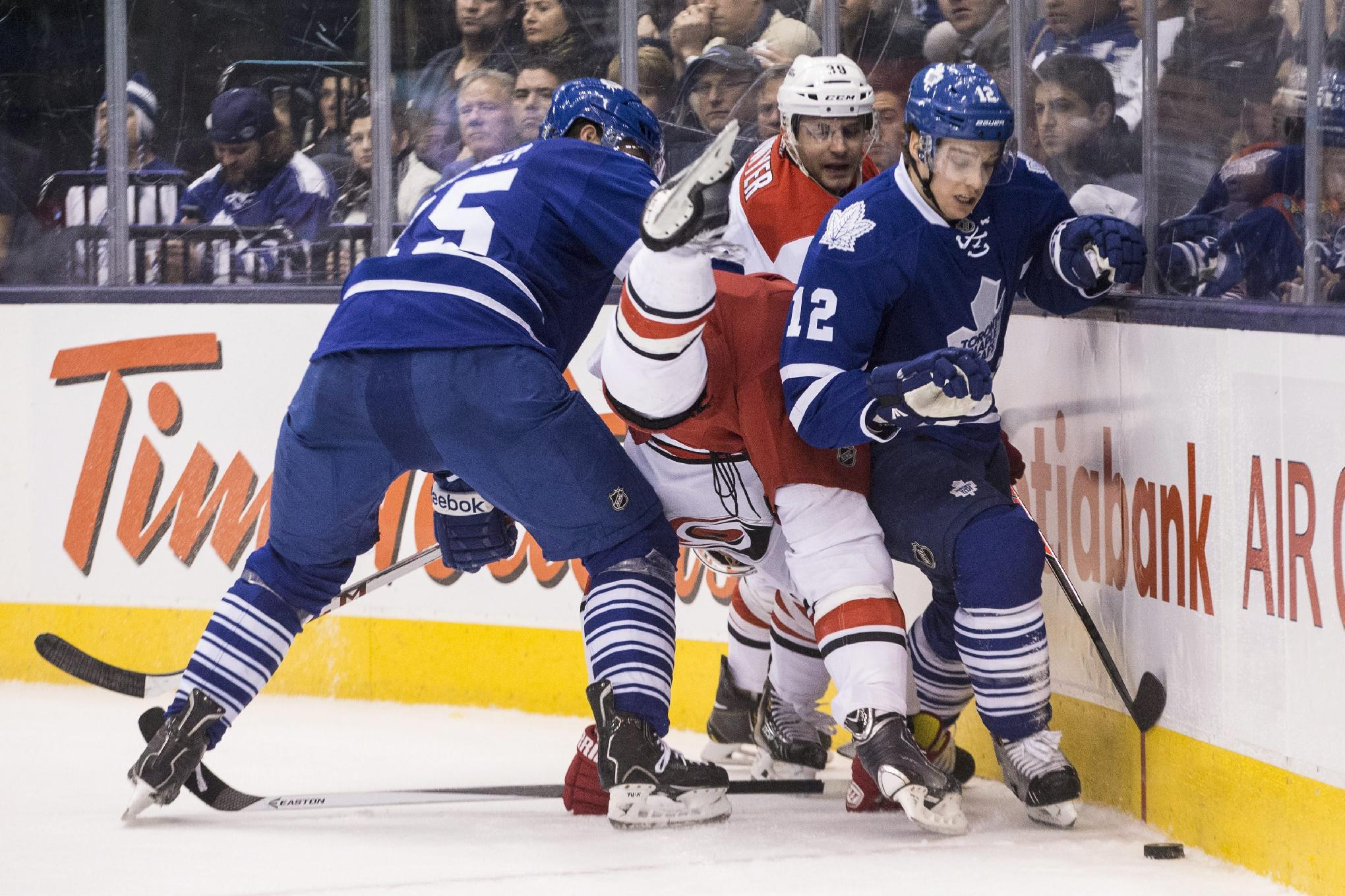 Toronto Maple Leafs' Paul Ranger, left, and Mason Raymond, right, upend Carolina Hurricanes' Drayson Bowman, center, as they battle for the puck against the boards during the third period of an NHL hockey game in Toronto on Sunday, Dec. 29, 2013