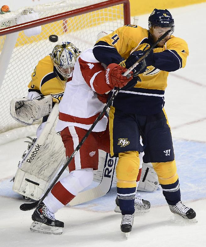 Nashville Predators defenseman Ryan Ellis (4) and Detroit Red Wings forward Patrick Eaves, center, deflect the puck away from Predators goalie Marek Mazanec, of the Czech Republic, left, in the first period of an NHL hockey game on Monday, Dec. 30, 2013, in Nashville, Tenn