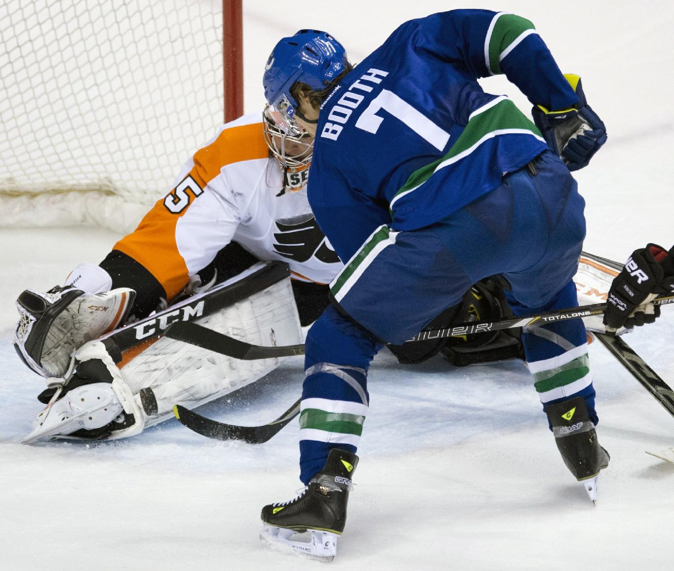 Vancouver Canucks left wing David Booth (7) tries to get a shot past Philadelphia Flyers goalie Steve Mason during the first period of an NHL hockey game against the Philadelphia Flyers in Vancouver, British Columbia, Monday, Dec. 30, 2013