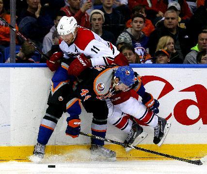 Carolina Hurricanes center Jordan Staal (11) is checked by New York Islanders defenseman Calvin de Haan (44) in the third period of an NHL hockey game in Uniondale, N.Y., Saturday Jan. 4, 2014. The Hurricanes won 3-2