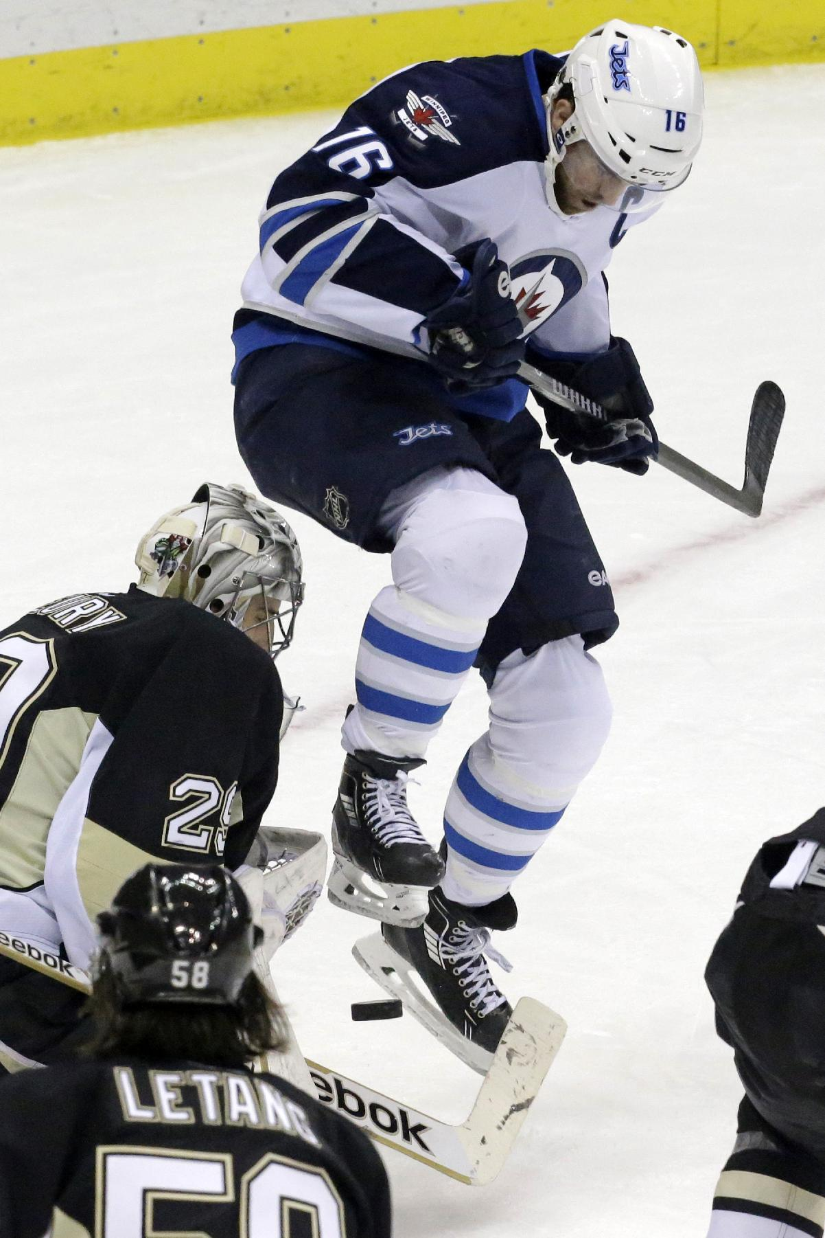 Winnipeg Jets Andrew Ladd (16) leaps out of the way of a shot in front of Pittsburgh Penguins goalie Marc-Andre Fleury (29) during the first period of an NHL hockey game in Pittsburgh, Sunday, Jan. 5, 2014