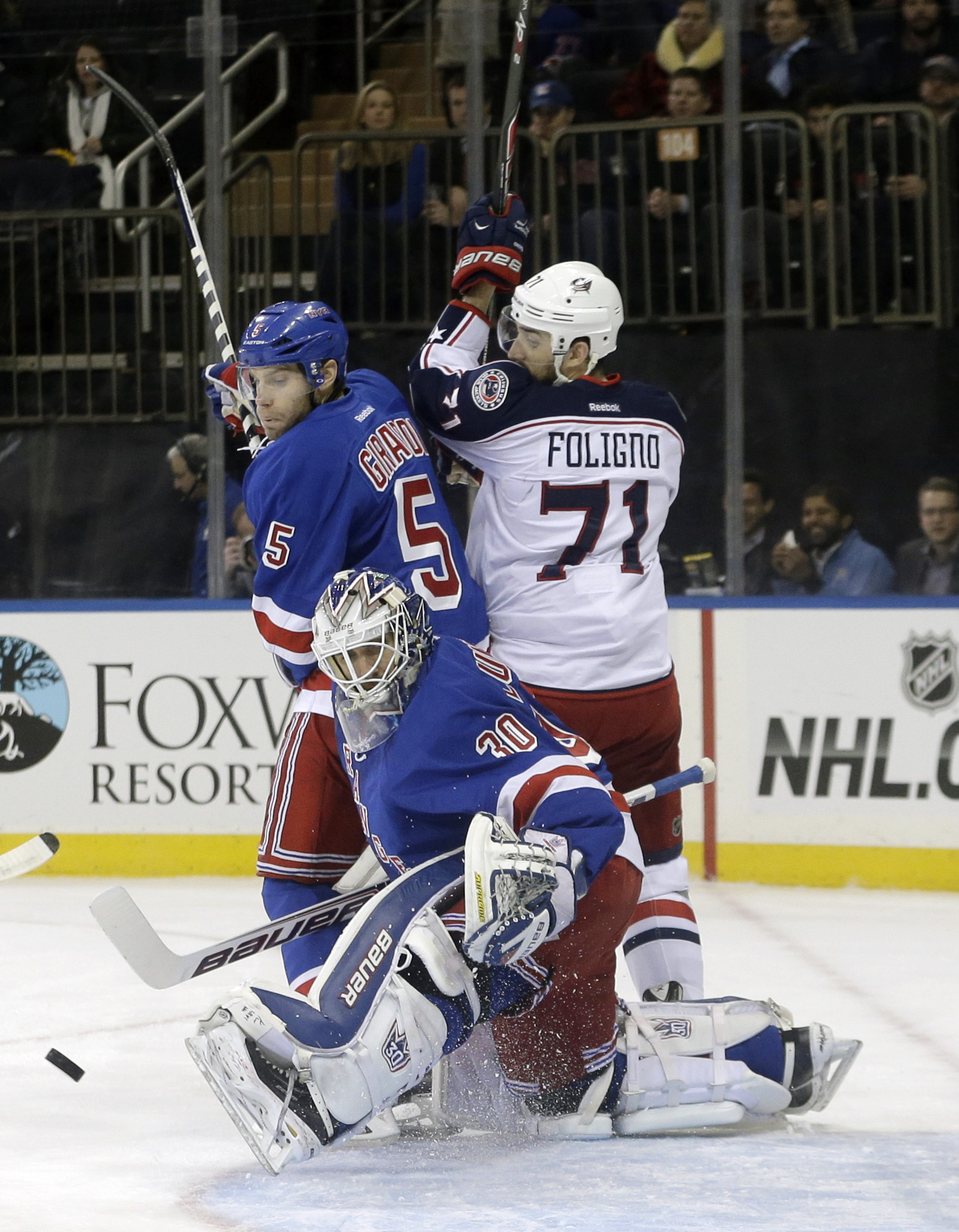 New York Rangers goalie Henrik Lundqvist (30) deflects a shot on the goal as Dan Girardi (5) and Columbus Blue Jackets' Nick Foligno (71) fight for position during the first period of an NHL hockey game, Monday, Jan. 6, 2014, in New York