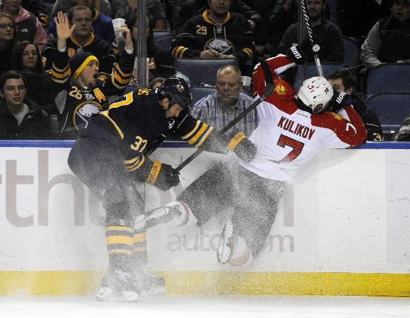 Buffalo Sabres left winger Matt Ellis (37) knocks Florida Panthers Dmitry Kulikov (7), of Russia, off his skates as they battle for the puck during the first period of an NHL hockey game in Buffalo, N.Y., Thursday, Jan. 9, 2014