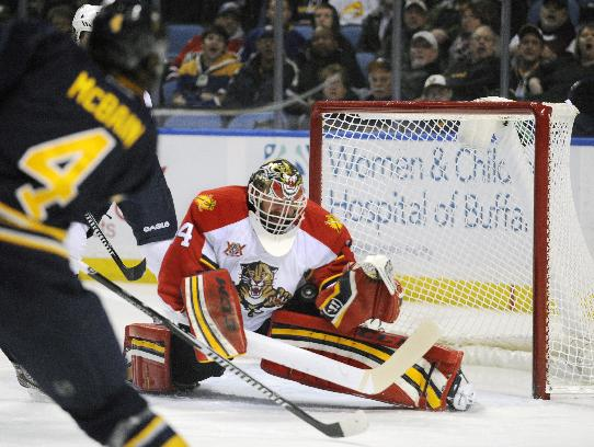 Buffalo Sabres defenseman Jamie McBain (4) shoots the puck at Florida Panthers goaltender Tim Thomas (34) during the first period of an NHL hockey game in Buffalo, N.Y., Thursday, Jan. 9, 2014