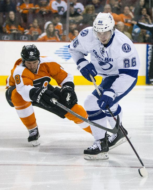 Tampa Bay Lightning's Nikita Kucherov, right, of Russia controls the puck with Philadelphia Flyers' Nicklas Grossmann, left, of Sweden, reaching for it during the first period of an NHL hockey game, Saturday, Jan. 11, 2014, in Philadelphia