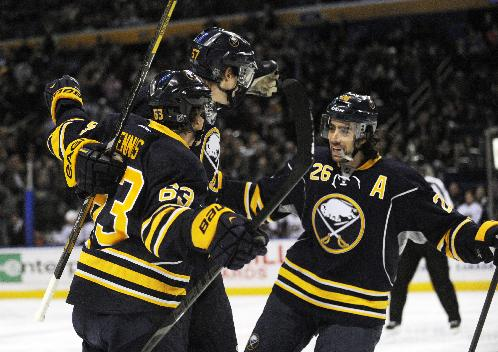 Buffalo Sabres' Tyler Ennis (63) and Matt Moulson (26) celebrate with Tyler Myers, center, after Myers scored a goal against the Columbus Blue Jackets during the first period of an NHL hockey game in Buffalo, N.Y., Saturday, Jan. 18, 2014