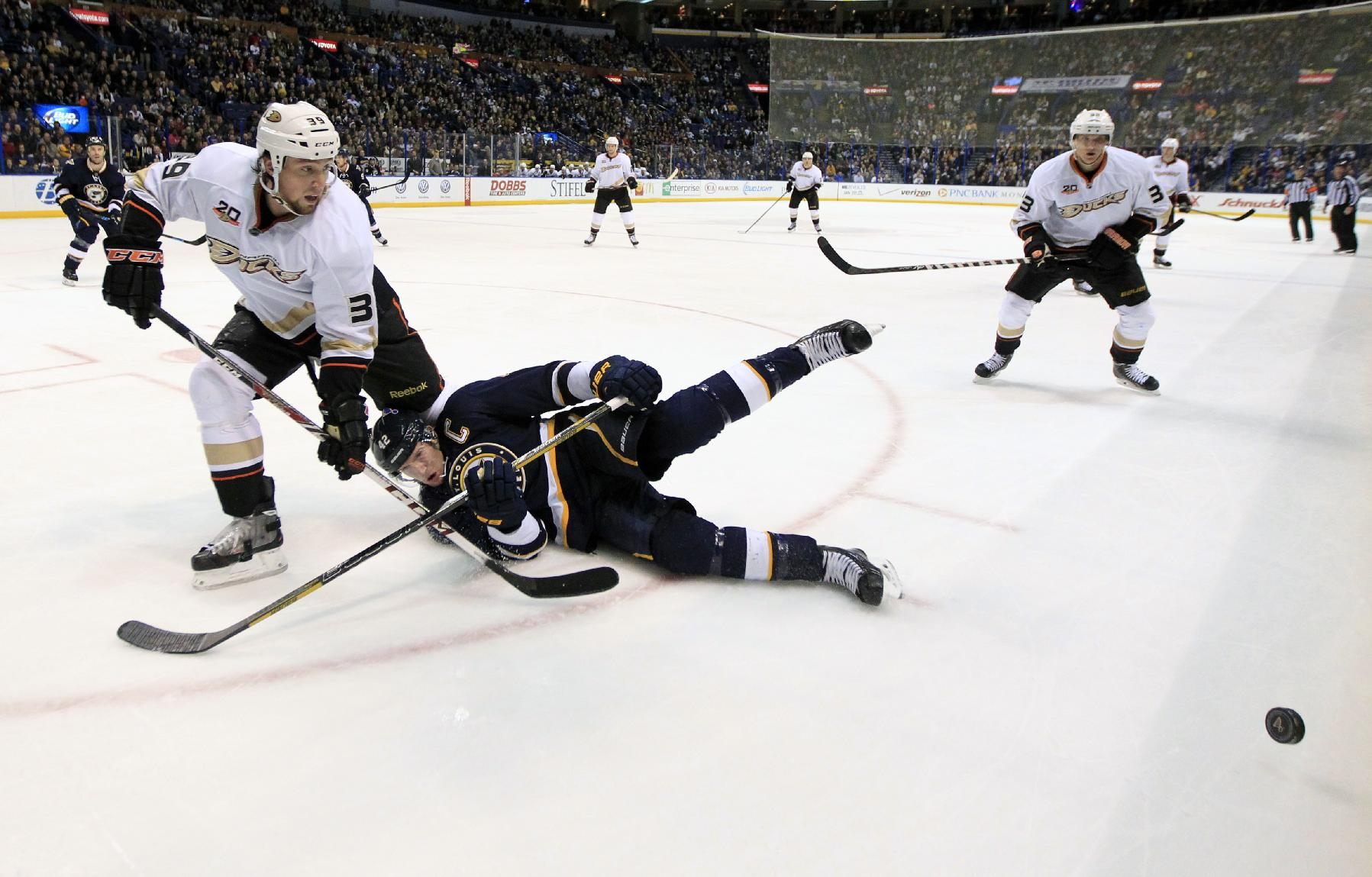 St. Louis Blues' David Backes, center, falls as he chases after a loose puck along side Anaheim Ducks' Matt Beleskey, left, and Jakob Silfverberg, right, of Sweden, during the third period of an NHL hockey game on Saturday, Jan. 18, 2014, in St. Louis. The Ducks won 3-2