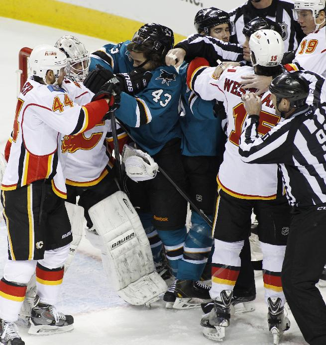 San Jose Sharks and Calgary Flames tussle during the first period of an NHL hockey game, Monday, Jan. 20, 2014 in San Jose, Calif.  Flames  Chris Butler (44) is at left, Flames' goalie Karri Ramo is second from left and Sharks' John McCarthy (43) is third from left. The Sharks beat the Flames 3-2