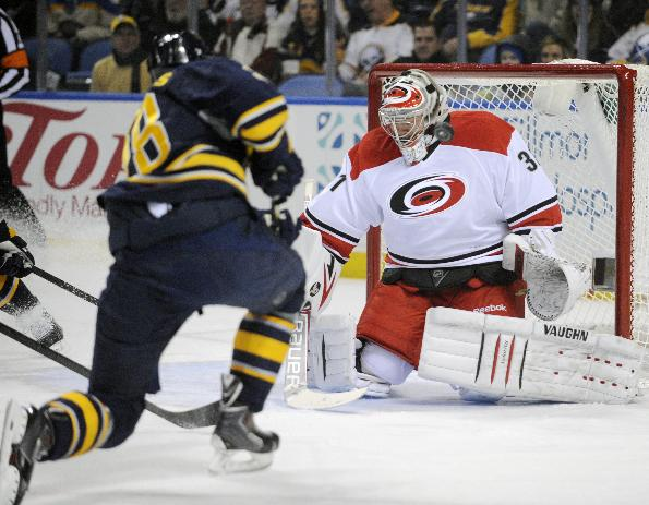 Buffalo Sabres' Zemgus Girgensons (28), of Latvia, shoots the puck off the mask of  Carolina Hurricanes' Anton Khudobin (31), of Russia, during the first period of an NHL hockey game in Buffalo, N.Y., Thursday, Jan. 23, 2014
