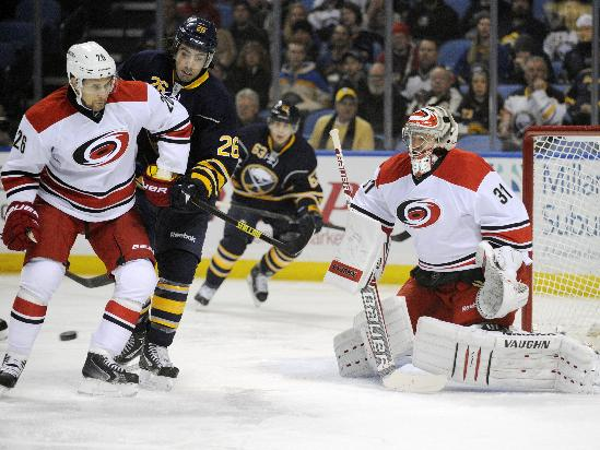 Carolina Hurricanes defenseman John-Michael Liles (26) battles with Buffalo Sabres left winger Matt Moulson (26) as goaltender Anton Khudobin (31), of Russia, eyes the incoming puck during the first period of an NHL hockey game in Buffalo, N.Y., Thursday, Jan. 23, 2014