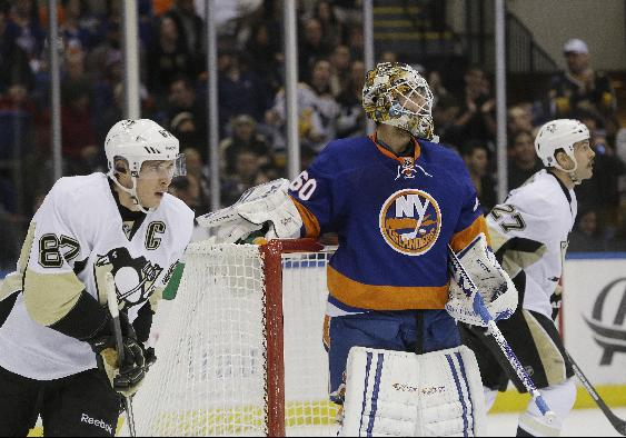 Pittsburgh Penguins' Sidney Crosby (87) and teammate Craig Adams (27) skate past New York Islanders goalie Kevin Poulin (60) after Crosby scored during the first period of an NHL hockey game, Thursday, Jan. 23, 2014 in Uniondale, N.Y