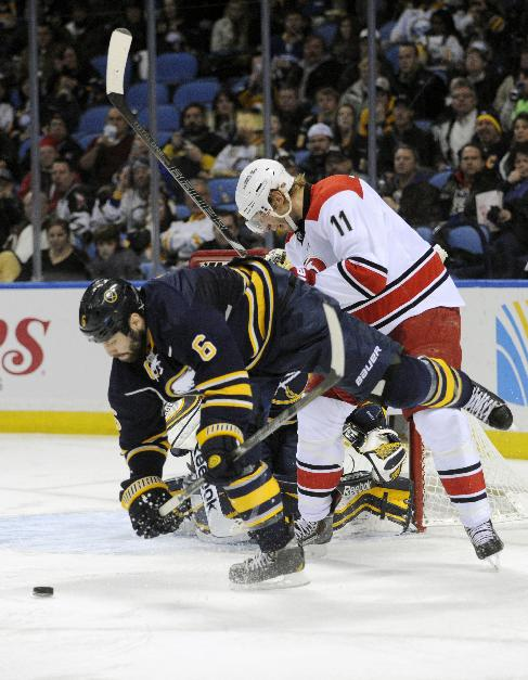 Buffalo Sabres defenseman Mike Weber (6) gets checked by Carolina Hurricanes center Jordan Staal (11) in front of the Sabres goal during the second period of an NHL hockey game in Buffalo, N.Y., Thursday, Jan. 23, 2014