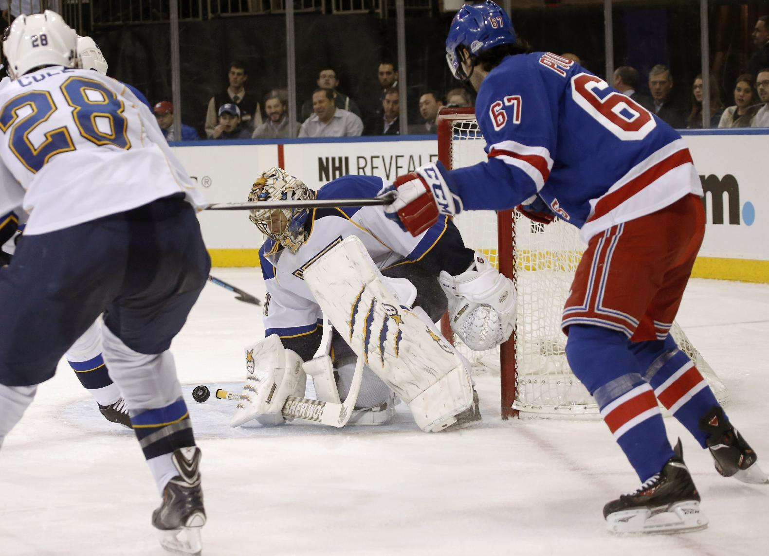 St. Louis Blues goalie Jaroslav Halak (41), of the Czech Republic, blocks a shot with New York Rangers left wing Benoit Pouliot (67) and Blues defenseman Ian Cole (28) watching during the second period of an NHL hockey game at Madison Square Garden in New York, Thursday, Jan. 23, 2014