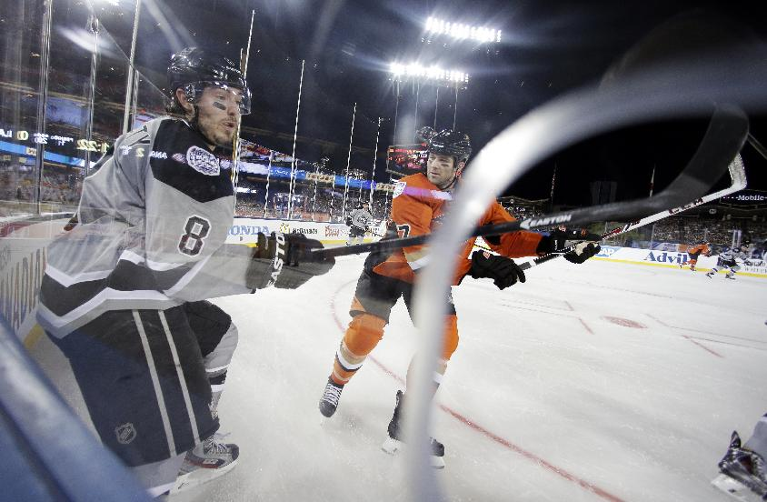 Los Angeles Kings defenseman Drew Doughty, left, and Anaheim Ducks left wing Dustin Penner battle for the puck during the first period of an NHL outdoor hockey game at Dodger Stadium in Los Angeles, Saturday, Jan. 25, 2014