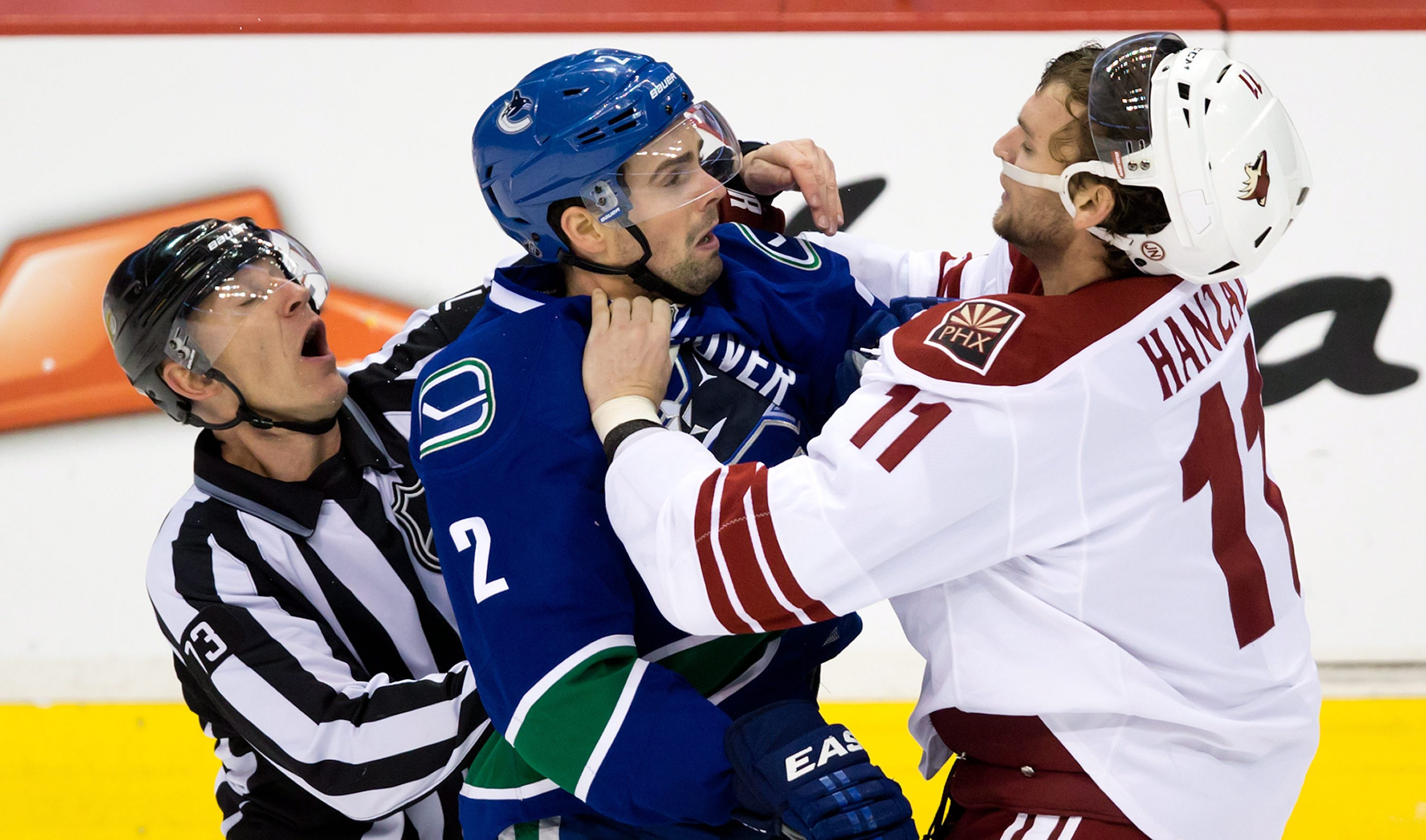 Linesman Vaughan Rody, left, tries to separate Vancouver Canucks' Dan Hamhuis, center, and Phoenix Coyotes' Martin Hanzal, of the Czech Republic, during the third period of an NHL hockey game in Vancouver, British Columbia, on Sunday, Jan. 26, 2014