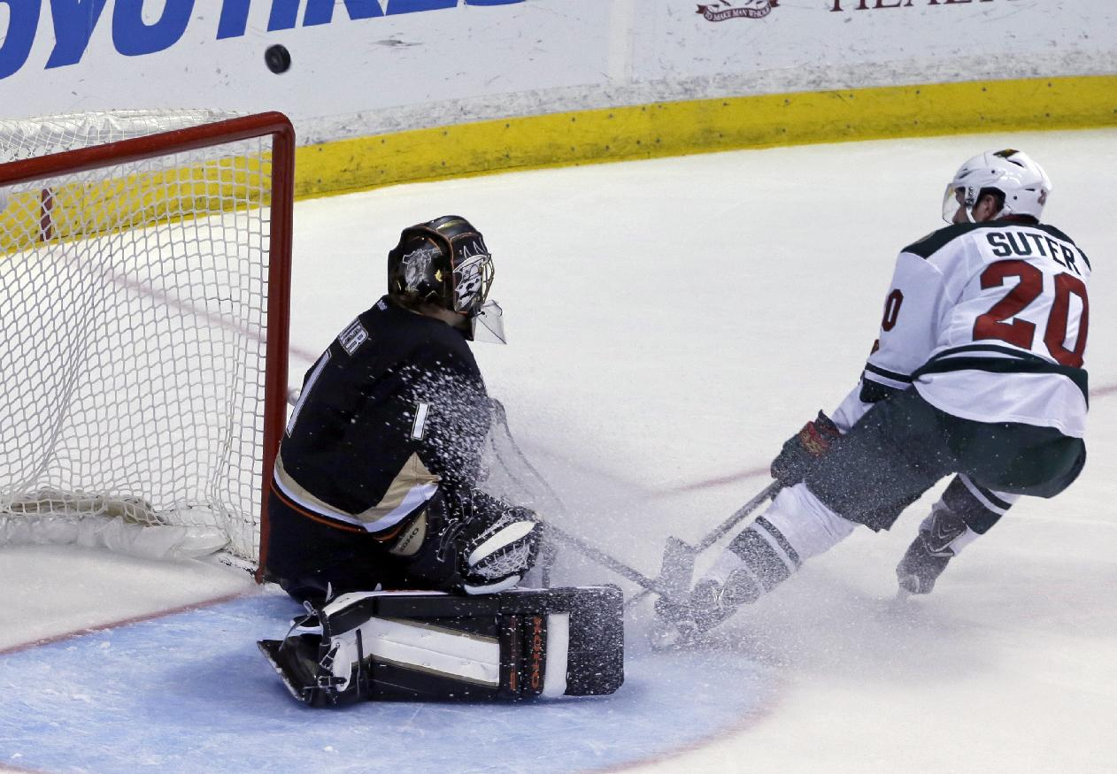 Anaheim Ducks goalie Jonas Hiller (1), of Switzerland, deflects the puck as Minnesota Wild defenseman Ryan Suter (20) skates by in the third period of an NHL hockey game in Anaheim, Calif., Tuesday, Jan. 28, 2014. The Wild won, 4-2