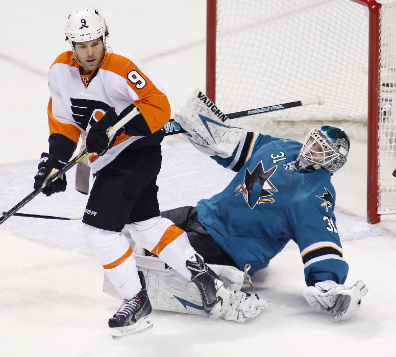 San Jose Sharks' Antti Niemi, front, falls back in front of Philadelphia Flyers' Steve Downie during the second period of an NHL hockey game, Monday, Feb. 3, 2014, in San Jose, Calif