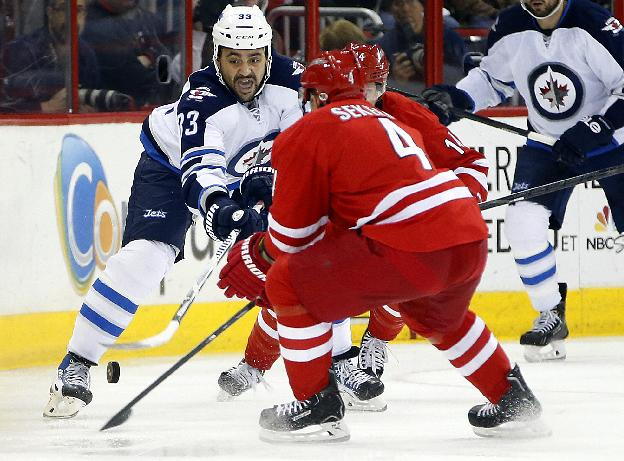 Winnipeg Jets' Dustin Byfuglien (33) tries to clear the puck past Carolina Hurricanes' Andrej Sekera (4) of Slovakia, during the first period of an NHL hockey game in Raleigh, N.C., Tuesday, Feb. 4, 2014