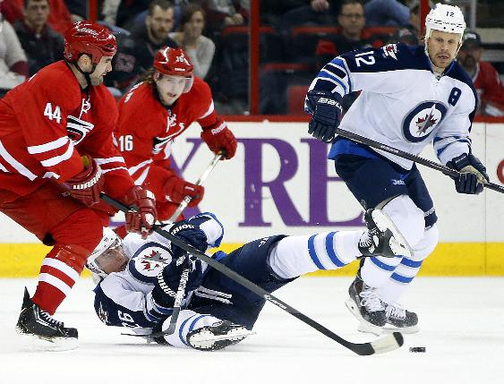 Carolina Hurricanes' Jay Harrison (44) takes Winnipeg Jets' Blake Wheeler (26) off the puck with Olli Jokinen (12) of Finland, during the first period of an NHL hockey game in Raleigh, N.C., Tuesday, Feb. 4, 2014
