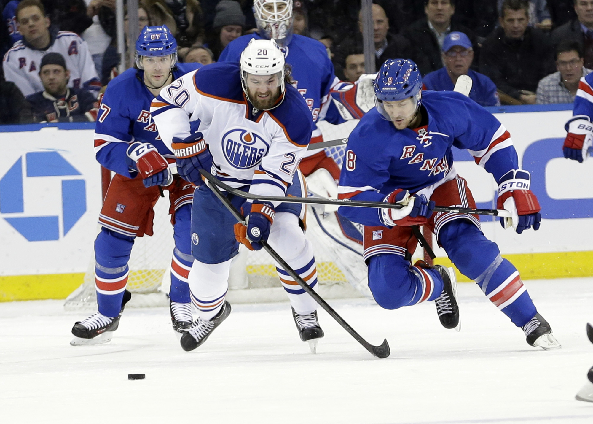 Edmonton Oilers' Luke Gazdic (20) and New York Rangers' Kevin Klein (8) fight for control of the puck during the second period of an NHL hockey game on Thursday, Feb. 6, 2014, in New York