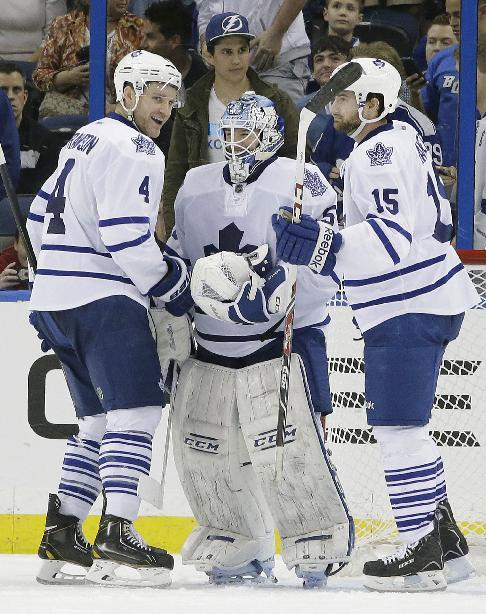 Toronto Maple Leafs goalie Jonathan Bernier (45) celebrates with teammates Cody Franson (4) and Paul Ranger (15) after the team defeated the Tampa Bay Lightning 4-1 during an NHL hockey game, Thursday, Feb. 6, 2014, in Tampa, Fla