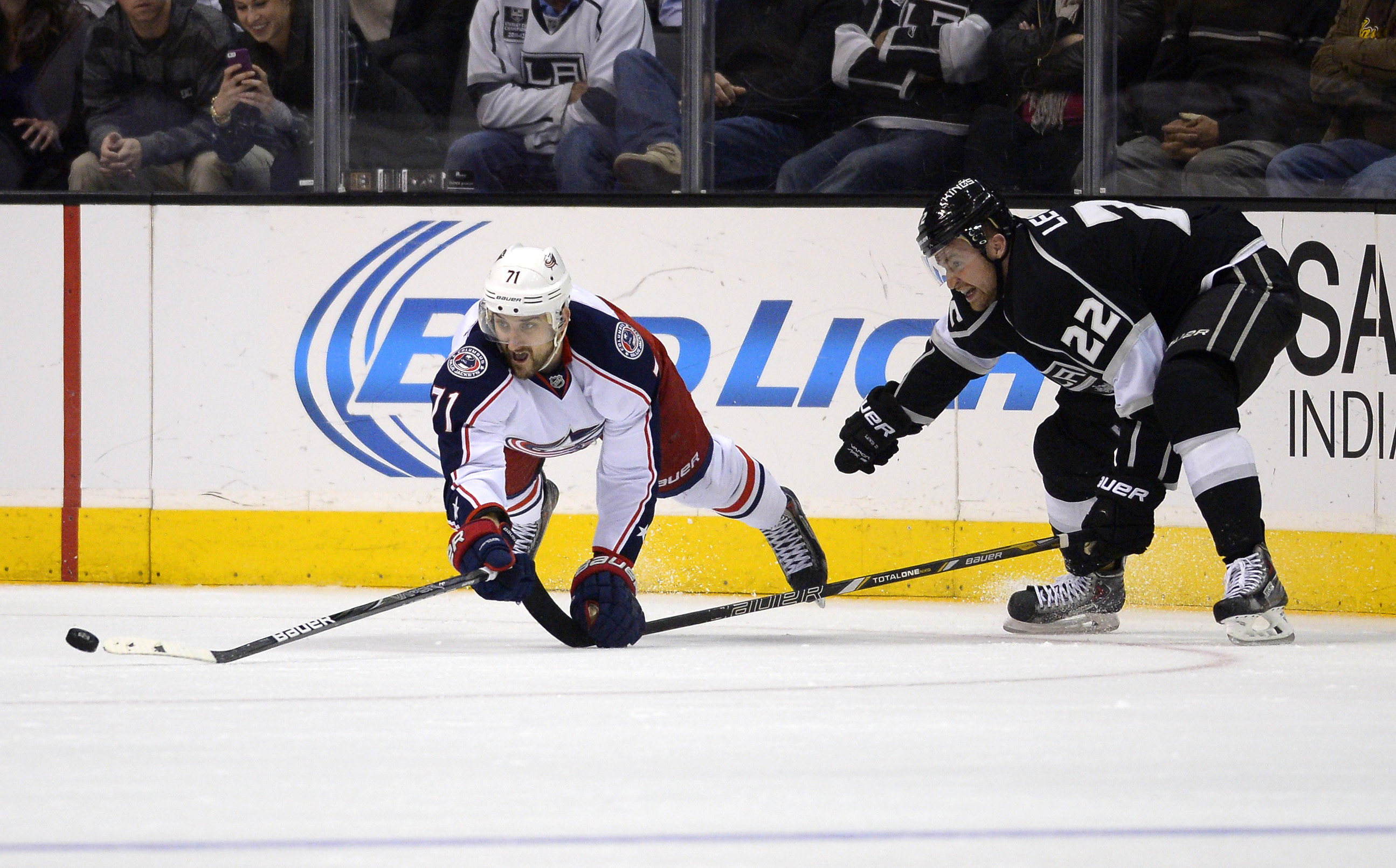 Columbus Blue Jackets left wing Nick Foligno, left, dives for the puck as Los Angeles Kings center Trevor Lewis reaches in during the third period of an NHL hockey game, Thursday, Feb. 6, 2014, in Los Angeles