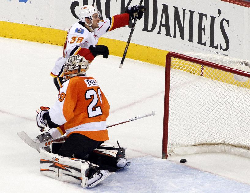 Calgary Flames' TJ Galiardi, top, reacts as a puck shot by teammate Lance Bouma gets past Philadelphia Flyers goalie Ray Emery during the third period of an NHL hockey game, Saturday, Feb. 8, 2014, in Philadelphia. The Flyers won 2-1