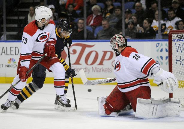 Carolina Hurricanes' Brett Bellemore (73) and Cam Ward (30) defend as Buffalo Sabres' Cody Hodgson (19) battles for a rebound during the first period of an NHL hockey game in Buffalo, N.Y., Tuesday, Feb. 25, 2014