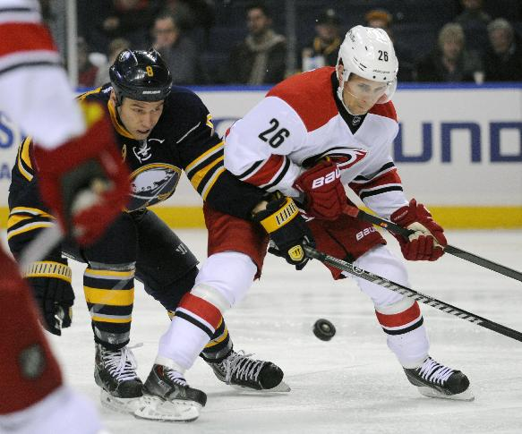 Buffalo Sabres'  Cody McCormick (8) battles for the puck with Carolina Hurricanes' John-Michael Liles (26) during the first period of an NHL hockey game in Buffalo, N.Y., Tuesday, Feb. 25, 2014