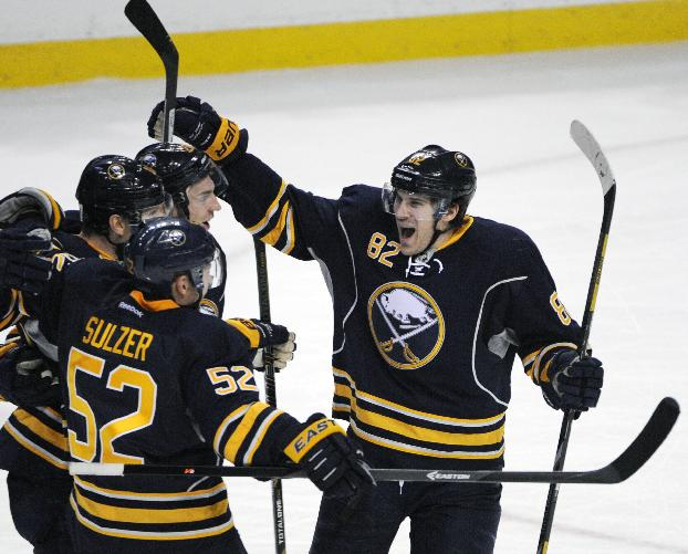 Buffalo Sabres Marcus Foligno (82) celebrates with Zemgus Girgensons, Christian Ehrhoff, and Alexander Sulzer after he scored the game winning goal against the  Carolina Hurricanes during the third period of an NHL hockey game in Buffalo, N.Y., Tuesday, Feb. 25, 2014. Buffalo won 3-2