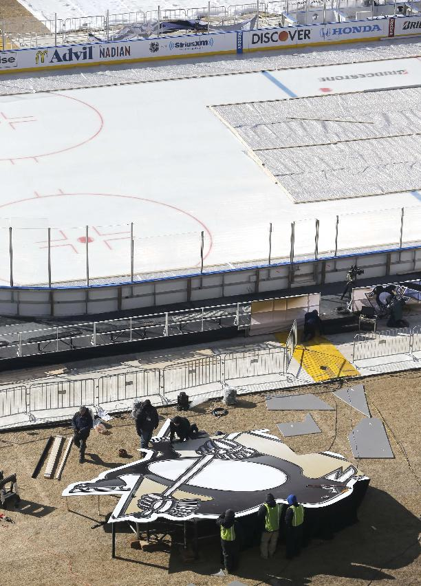 Workers construct a large Pittsburgh Penguins logo as they continue to transform Soldier Field for Saturday's Stadium Series NHL hockey game between the Chicago Blackhawks and the Penguins, Thursday, Feb. 27, 2014, in Chicago
