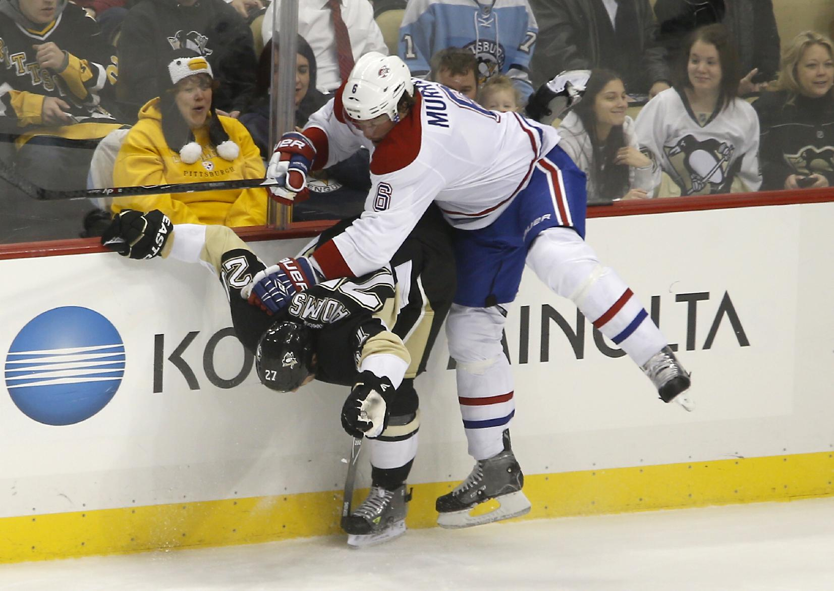 Montreal Canadiens' Douglas Murray (6) checks Pittsburgh Penguins' Craig Adams (27) during the first period of an NHL hockey game, Thursday, Feb. 27, 2014 in Pittsburgh