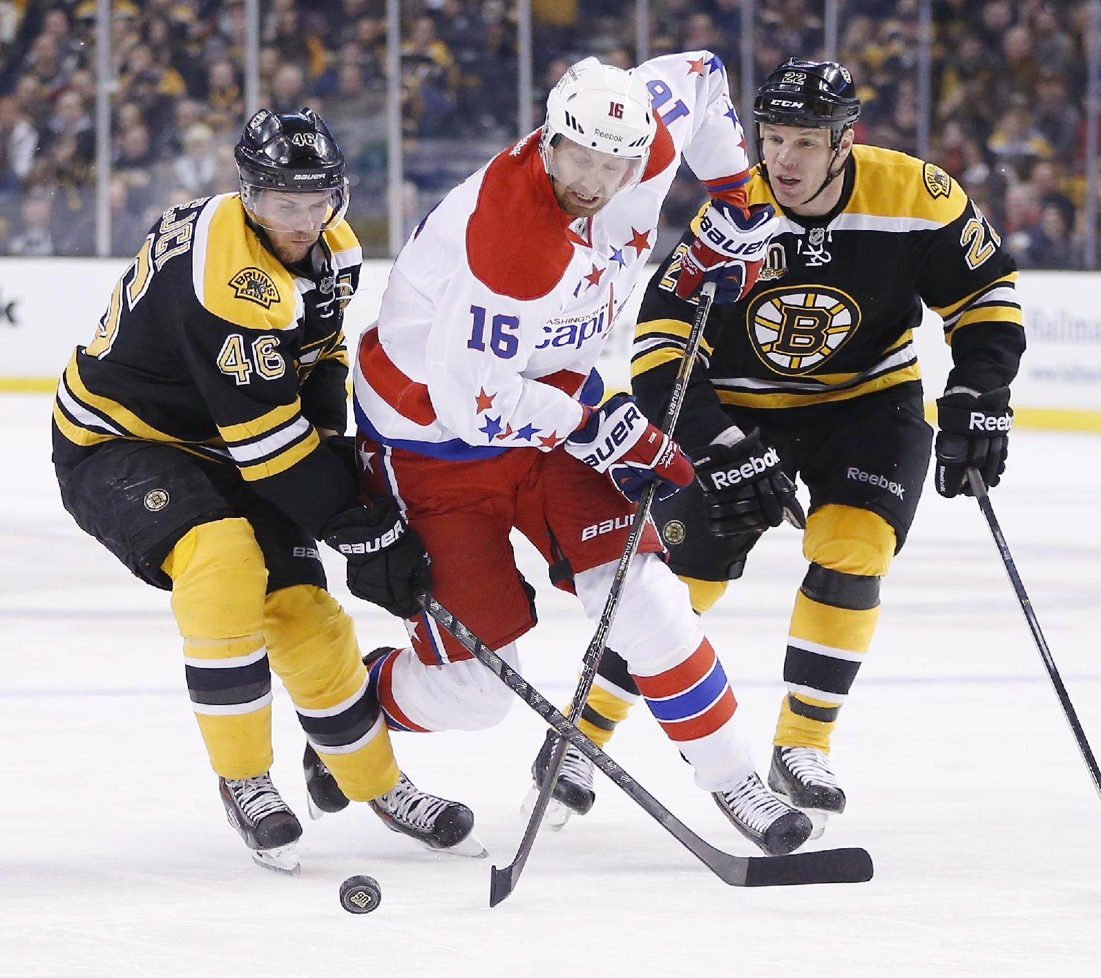 Washington Capitals' Eric Fehr (16) battles Boston Bruins' David Krejci (46) and Shawn Thornton (22) for the puck in the first period of an NHL hockey game in Boston, Saturday, March 1, 2014