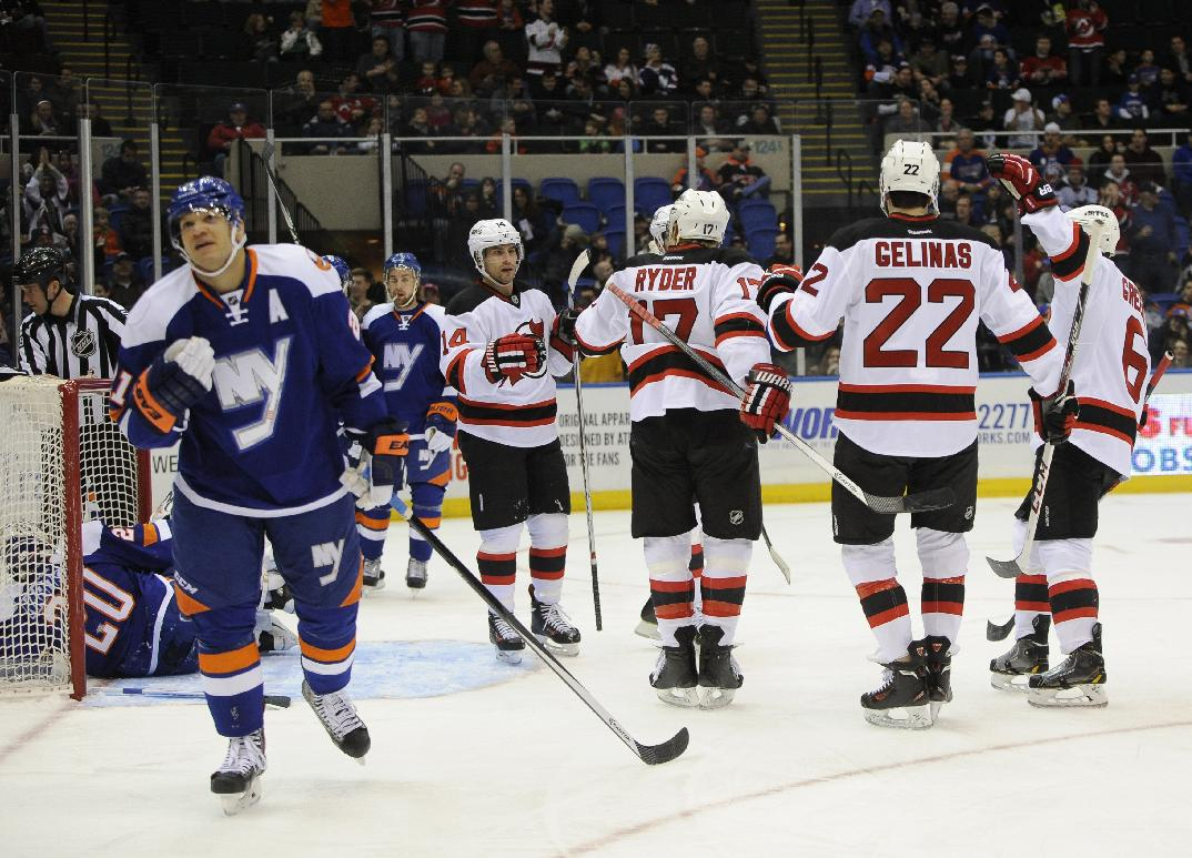 New Jersey Devils' Adam Henrique (14) celebrates his goal with teammates as New York Islanders' Kyle Okposo, left foreground, skates away in the first period of an NHL hockey game on Saturday, March 1, 2014, in Uniondale, N.Y
