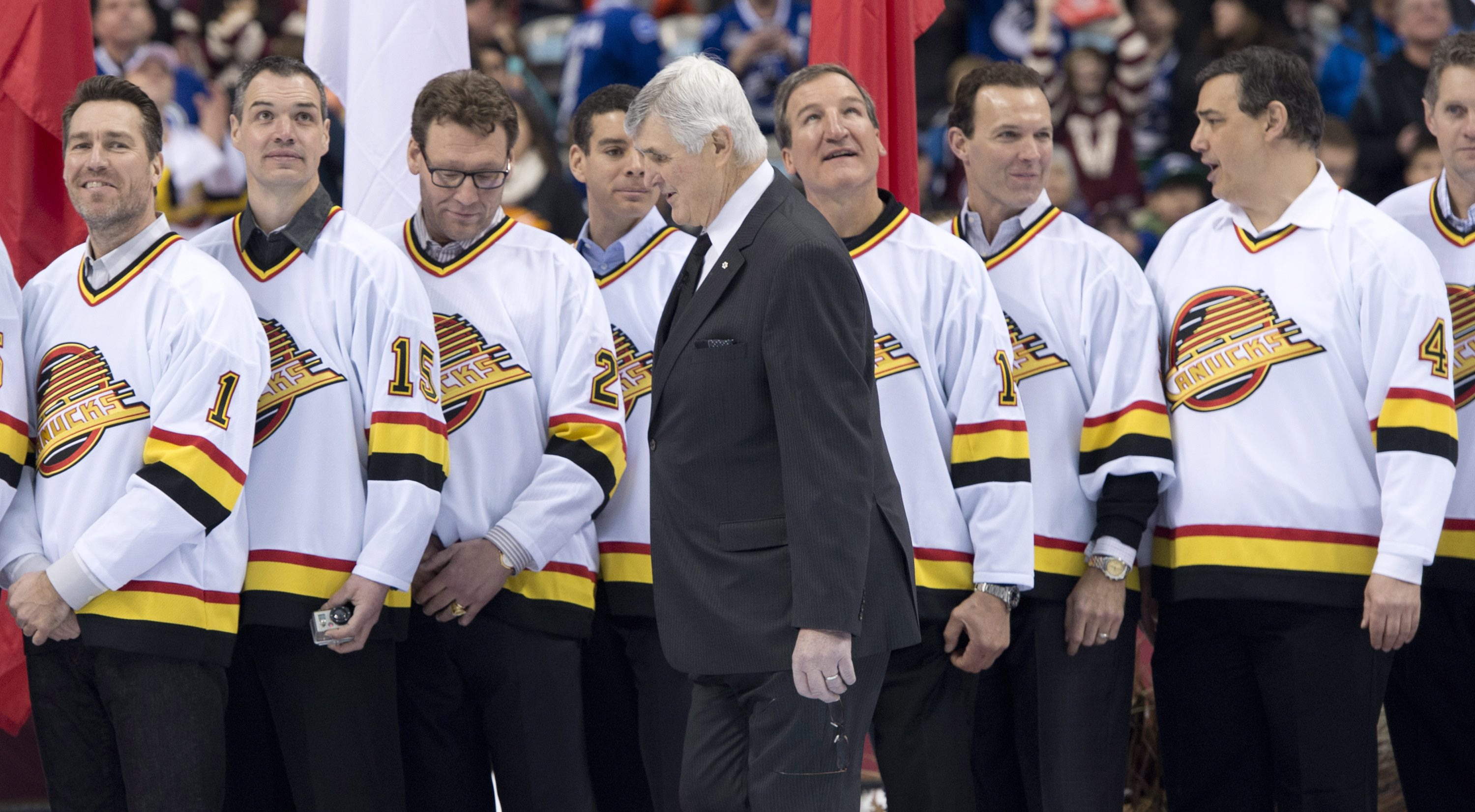 Pat Quinn walks past former members of the Vancouver Canucks before the NHL Heritage Classic hockey game between the Canucks and the Ottawa Senators in Vancouver, British Columbia,, on Sunday, March 2, 2014