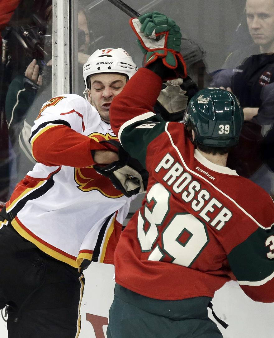 Calgary Flames' Lance Bouma, left, gets checked into the boards by Minnesota Wild's Nate Prosser in the first period of an NHL hockey game, Monday, March 3, 2014, in St. Paul, Minn